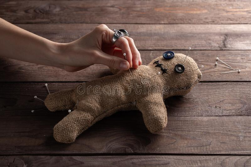 Voodoo doll on a wooden background with dramatic lighting. The concept of witchcraft and black art. Burlap doll on a wooden stock photo