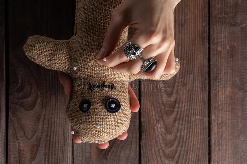 Voodoo doll on a wooden background with dramatic lighting. The concept of witchcraft and black art. Burlap doll on a wooden stock photos