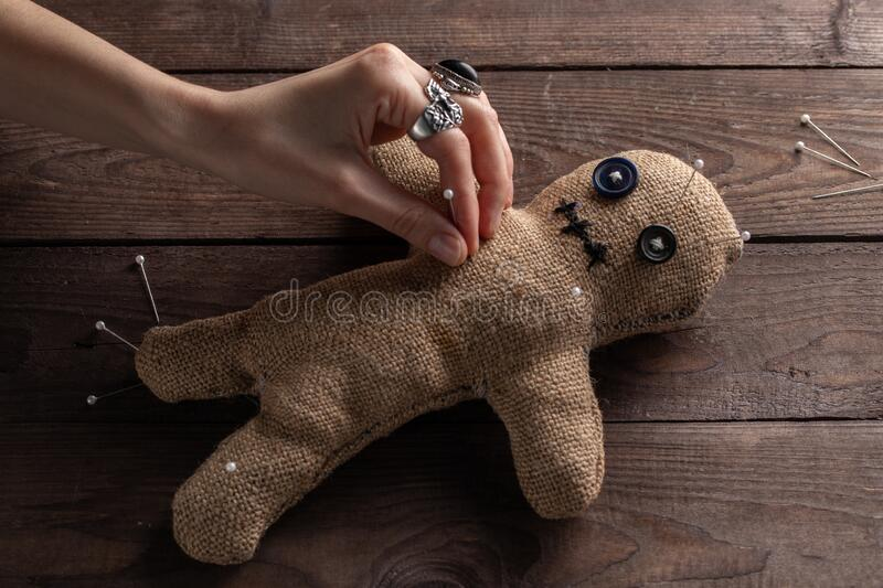 Voodoo doll on a wooden background with dramatic lighting. The concept of witchcraft and black art. Burlap doll on a wooden stock image