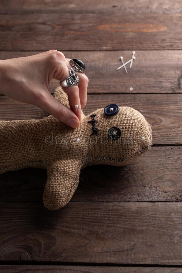 Voodoo doll on a wooden background with dramatic lighting. The concept of witchcraft and black art. Burlap doll on a wooden royalty free stock images