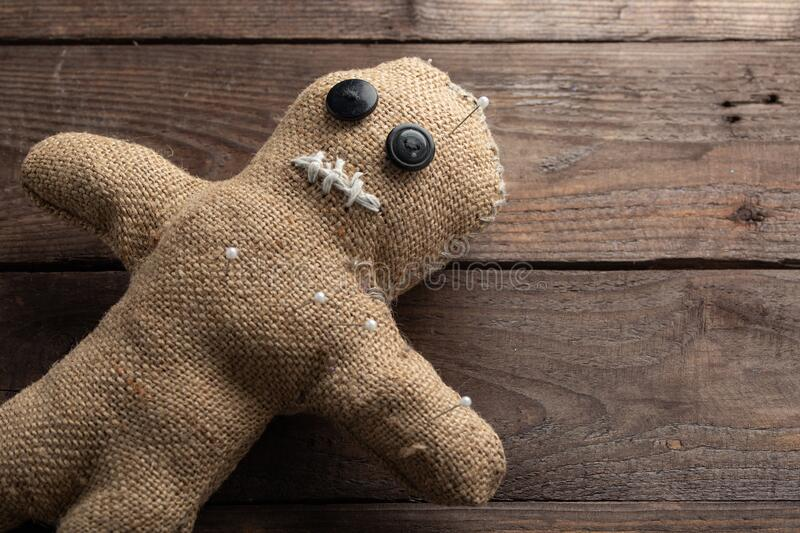 Voodoo doll on a wooden background with dramatic lighting. The concept of witchcraft and black art. Burlap doll on a wooden stock photography