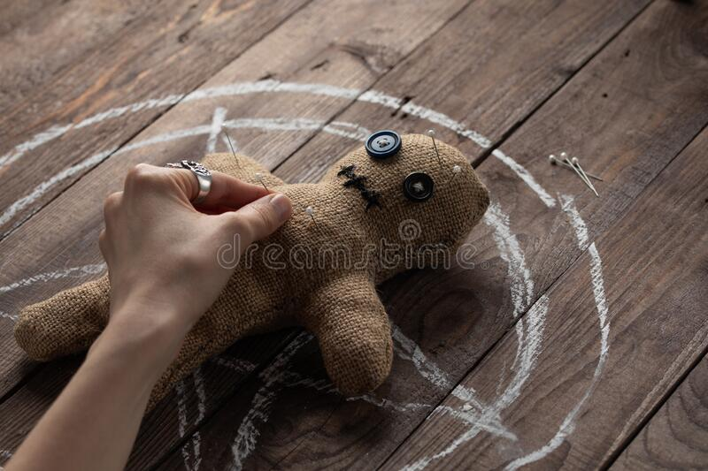 Voodoo doll on a wooden background with dramatic lighting. The concept of witchcraft and black art and the occult. Burlap doll on stock photos