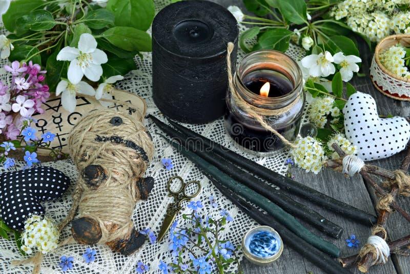 Voodoo la muñeca, las velas negras, las flores y los objetos misteriosos foto de archivo