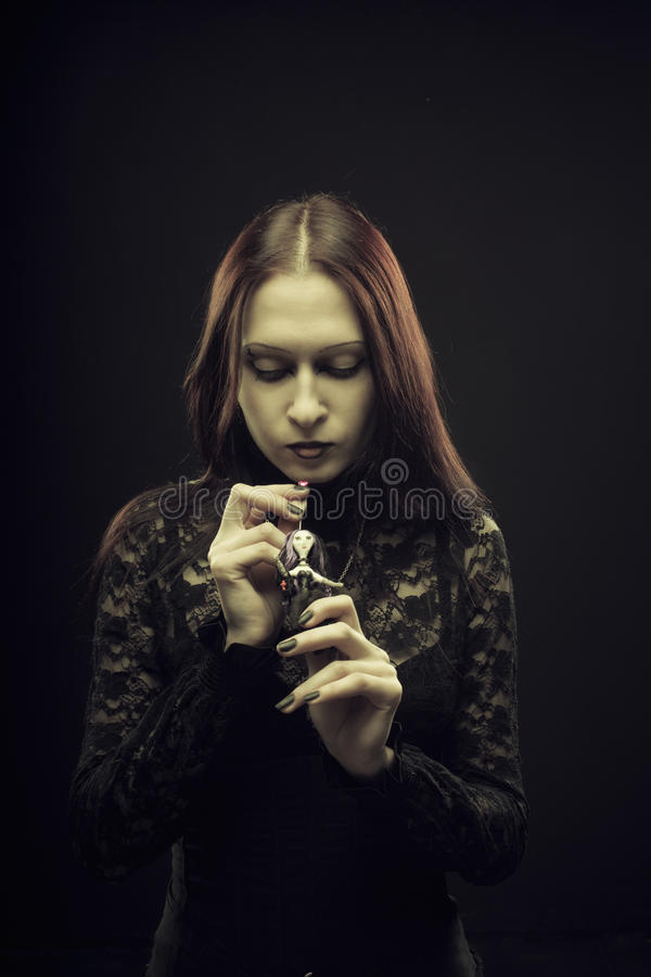Voodoo mood. Gothic pale girl holding voodoo doll over black background stock images