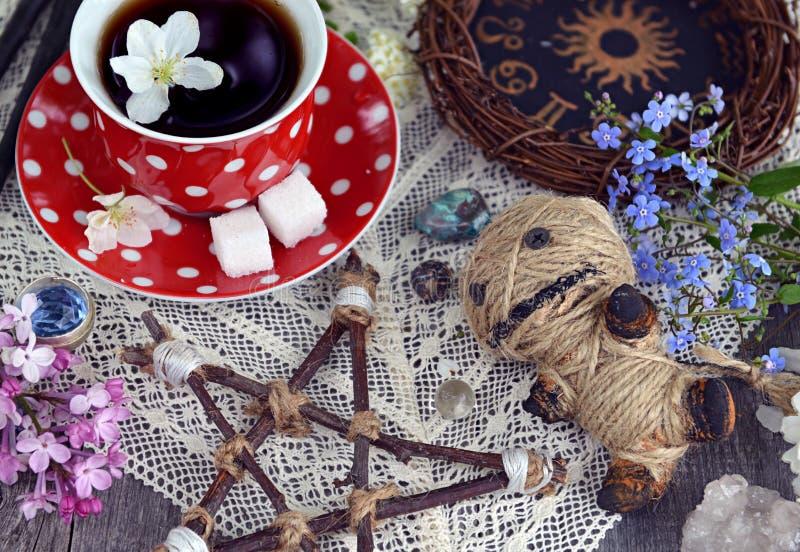 Voodoo Puppe mit Pentagram, Tasse Tee, mysteriöse Gegenstände und Blumen stockfotos