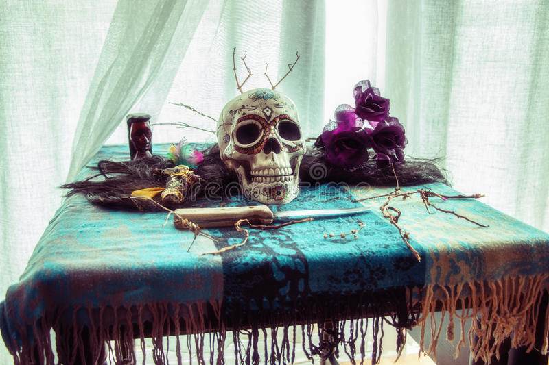 Voodoo Skull Table Ritual. Voodoo related objects on a table including a skull, a knife and candles stock photography