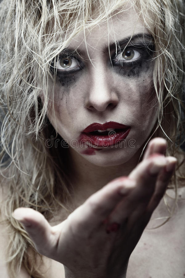 Voodoo witch. Voodoo female witch with dirty makeup and blood on the hand. Artistic colors and darkness added royalty free stock photos
