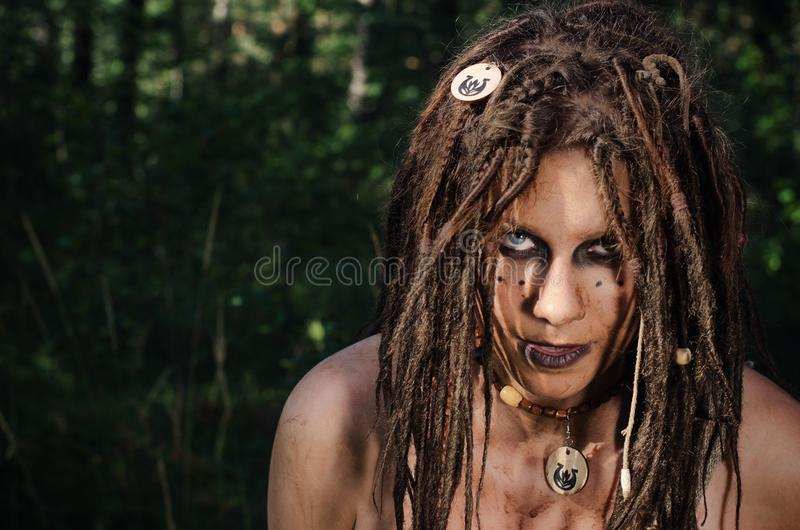 Voodoo witch in the woods. Evil and dirty. Hides in the woods stock image