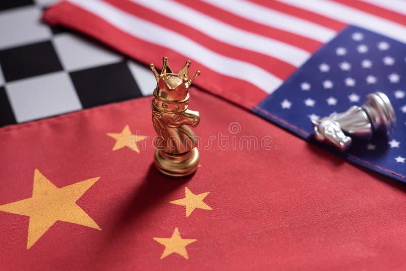 Voor achtergrond of Web Ridder met kroontribune als winnaar over de vijanden op de nationale vlaggen van China en van de V.S. Het stock fotografie