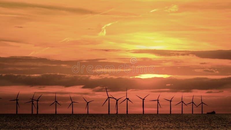 Voor de kust windfarm oranjerode zonsondergang stock foto's