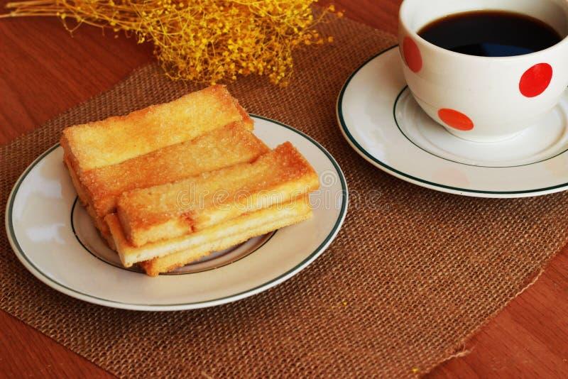 Voor de lijst, is er een zwarte koffie in het glas, een knapperig broodje royalty-vrije stock fotografie
