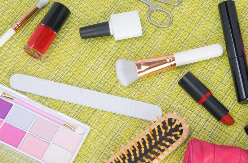 Voor een groene achtergrond, hulpmiddelen voor manicure en make-up, nagellakken, lippenstift, poederborstels, kleurrijke oogschad royalty-vrije stock afbeelding