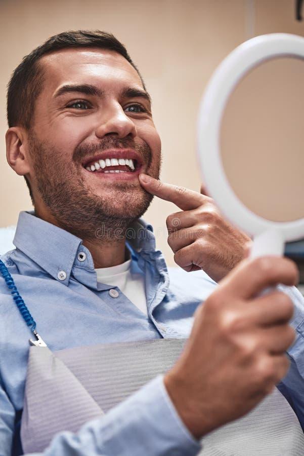 Voor een leven van glimlachen! Knappe mannelijke pati?nt die zijn mooie glimlachzitting bekijken op het tandkantoor Sluit omhoog stock foto