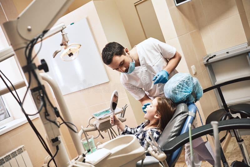 Voor een supersterglimlach Jong geitje op het tandkantoor De tandarts verklaart aan zijn pati?nt hoe te om tanden te borstelen stock afbeelding