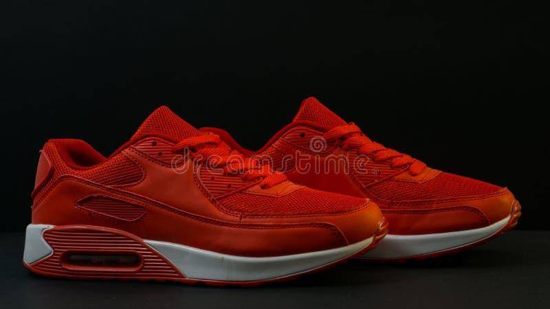 Voor een zwarte achtergrond, close-up, het rood van sportentennisschoenen, met een witte zool, is er een schaduw stock fotografie