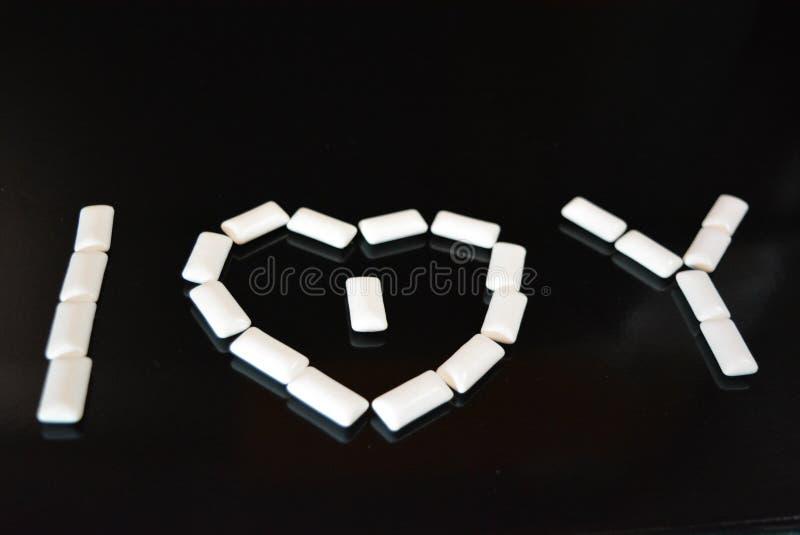 Voor een zwarte glanzende achtergrond, worden de witte hoofdkussens van kauwgom met bezinning gelegd en liggen in de vorm van lie stock afbeelding