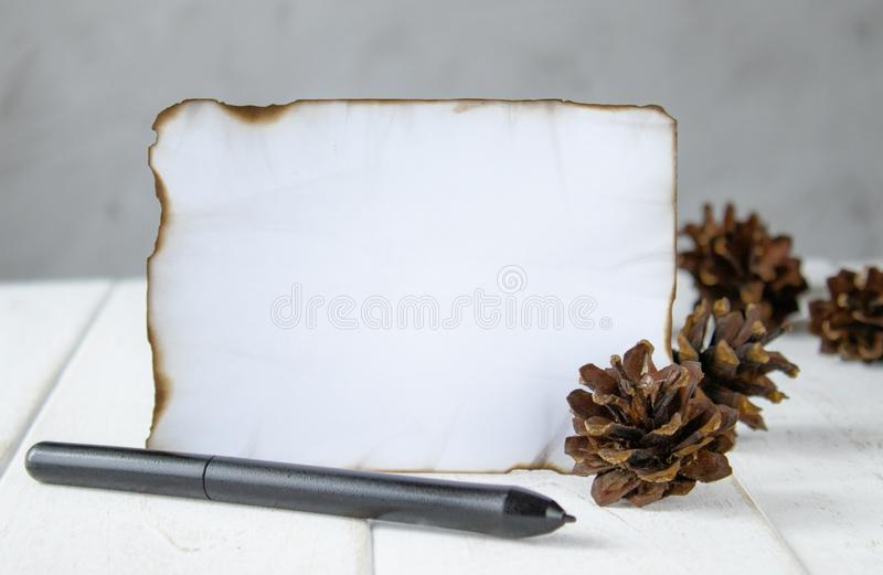 Voor witte houten raad, brandde een blad van document bij de randen, boskegels, een zwarte pen bij de randen Het verlaten van rui stock foto's
