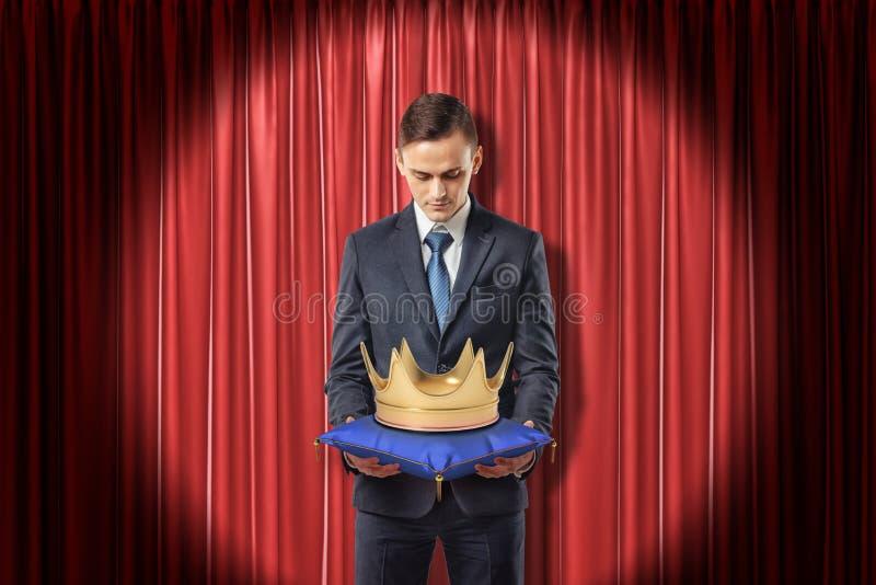 Vooraanzicht die van zakenman zich in schijnwerper tegen rood stadiumgordijn bevinden die neer gouden kroon op blauw hoofdkussen  stock afbeeldingen