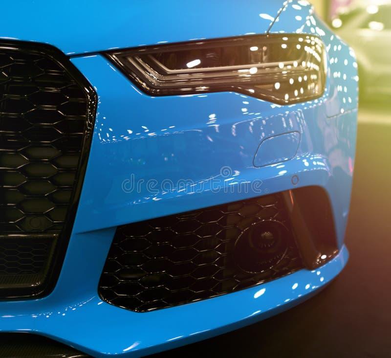 Vooraanzicht van blauwe moderne luxesport met zacht oranje zonlicht Auto buitendetails Koplamp van een moderne sportwagen stock afbeelding