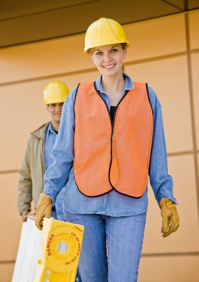 Vooraanzicht van bouwvakkers die ladder dragen stock fotografie