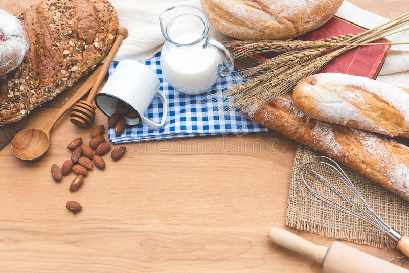 Vooraanzicht van broodbroodje, melk, amandelen en verse melk op houten lijst Ontbijtvoorbereiding, dagelijks product royalty-vrije stock afbeeldingen