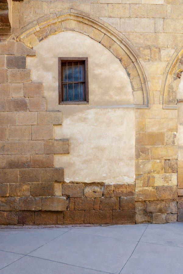 Vooraanzicht van de bakstenen muur van de grungesteen en klein venster bij Darb-al Ahmar District, Kaïro, Egypte stock foto's