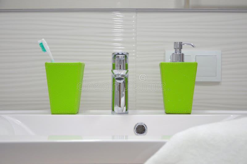 Vooraanzicht van de gootsteen met tapkraan, groen glas met tandenborstels en zeepautomaat stock fotografie
