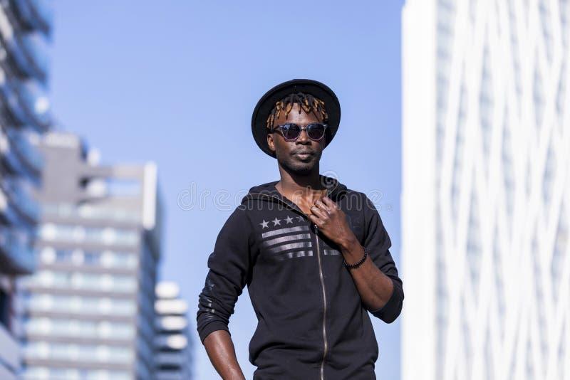 Vooraanzicht van de jonge zwarte mens met zonnebril en hoed die zich in de straat tegen blauwe hemel bevinden terwijl het kijken  royalty-vrije stock afbeeldingen