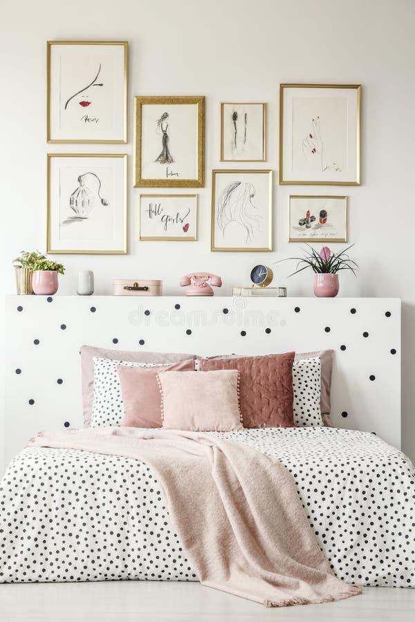 Vooraanzicht van een bed van de koningsgrootte met roze hoofdkussens, gestippelde bladen, royalty-vrije stock foto