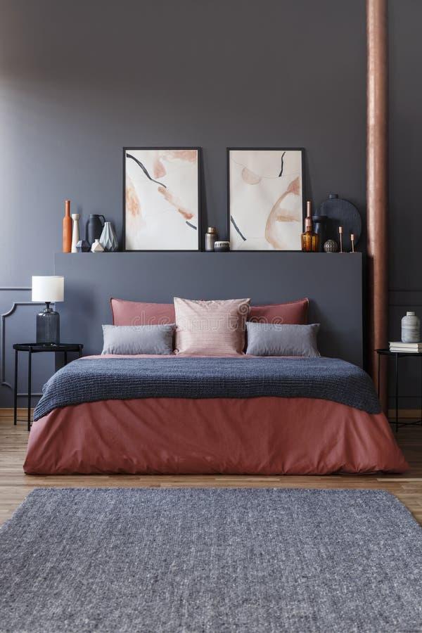 Vooraanzicht van een comfortabel bed met gemberbeddegoed, grijze deken en p stock afbeelding