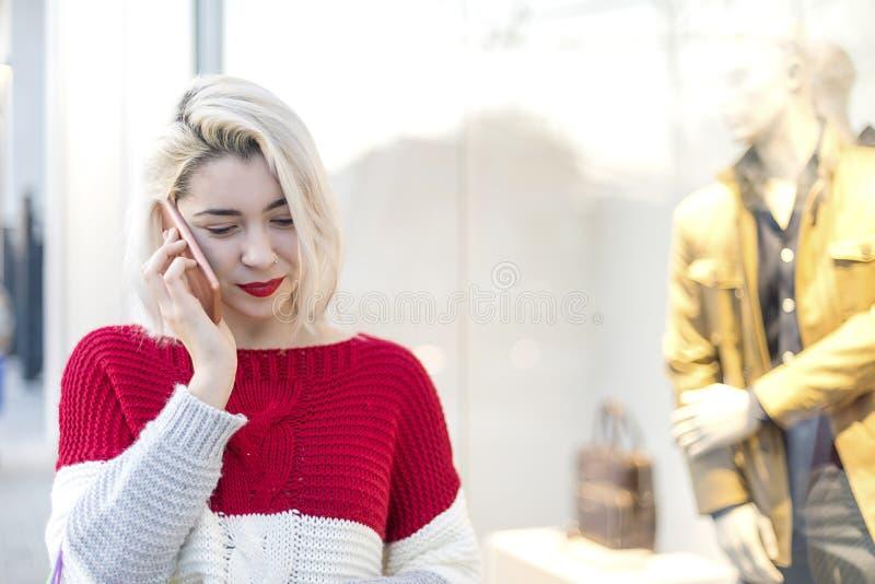 Vooraanzicht van een glimlachende jonge vrouw die zich in een winkelcentrum bevinden terwijl het gebruiken van mobiele telefoon royalty-vrije stock foto's