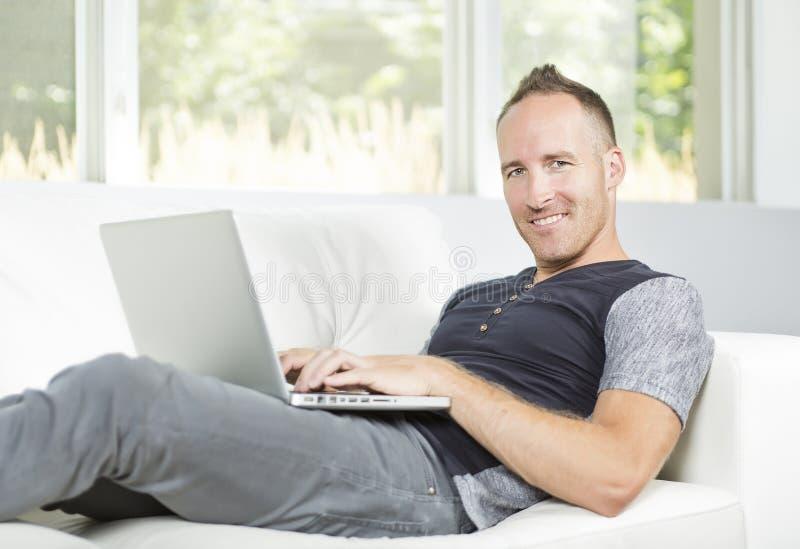 Vooraanzicht van een knappe mens die laptop zitting op laag thuis gebruiken stock afbeeldingen