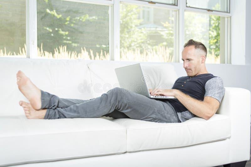 Vooraanzicht van een knappe mens die laptop zitting op laag thuis gebruiken stock foto