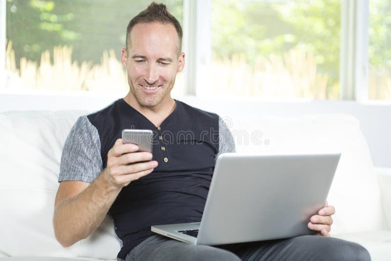 Vooraanzicht van een knappe mens die laptop zitting op laag thuis gebruiken royalty-vrije stock fotografie