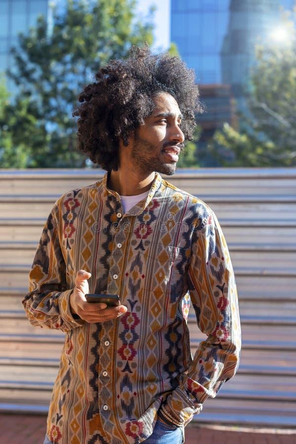 Vooraanzicht van een koele jonge glimlachende afromens die een mobiele telefoon met behulp van terwijl status in openlucht in een royalty-vrije stock afbeeldingen