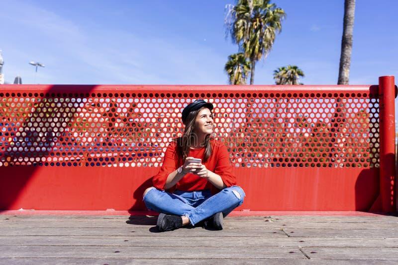 Vooraanzicht van een mooie jonge vrouw die stedelijke kleren dragen die op een brugvloer zitten terwijl in openlucht het gebruike royalty-vrije stock fotografie