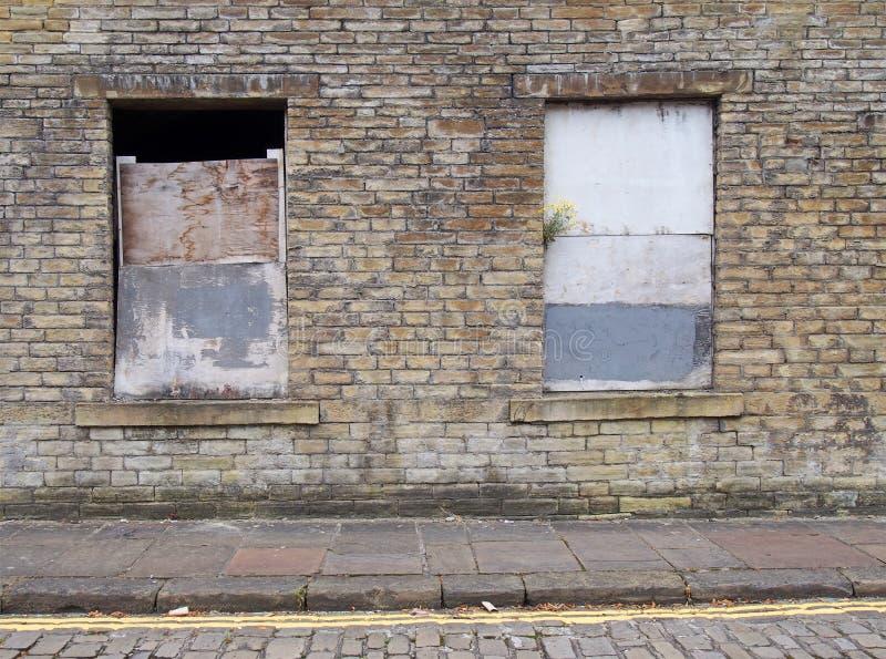 Vooraanzicht van een oud verlaten verlaten huis op een lege straat met ingescheept op vensters en dilapidated bakstenen muren stock fotografie
