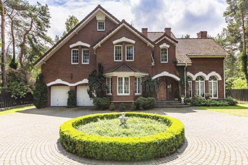 Vooraanzicht van een rood klassiek huis van de baksteen Engels stijl met een ste royalty-vrije stock foto's