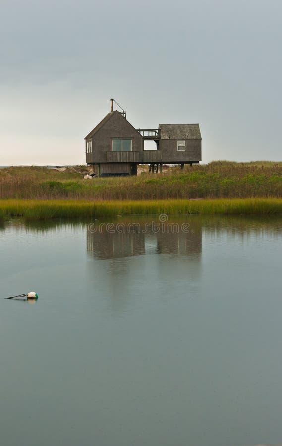 Vooraanzicht van een vooraanzicht van een een strandhuis en bezinning op achterdag bij zonsopgang stock foto's