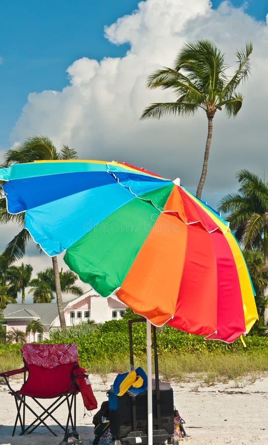 Vooraanzicht van een strandparaplu, een ligstoel en een totalisatorkar stock foto's