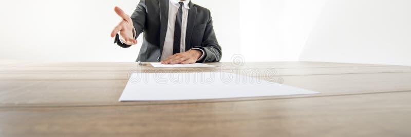 Vooraanzicht van een zakenmanzitting bij zijn bureau met document of royalty-vrije stock foto's