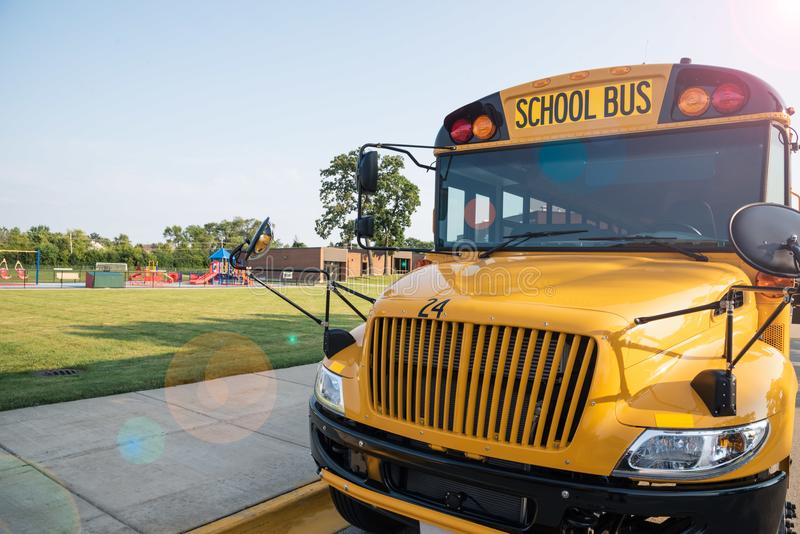 Vooraanzicht van gele schoolbus voor school die - brandmerken aangaande stock foto
