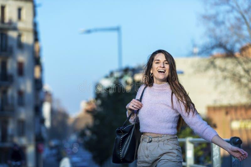 Vooraanzicht van het glimlachen gelukkige mooie jonge vrouw status in de straat terwijl het kijken camera in een zonnige dag stock foto