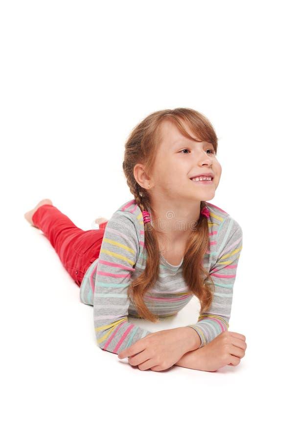 Vooraanzicht van het glimlachen kindmeisje het liggen op vloer royalty-vrije stock foto's