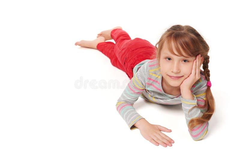 Vooraanzicht van het glimlachen kindmeisje het liggen op vloer royalty-vrije stock afbeelding