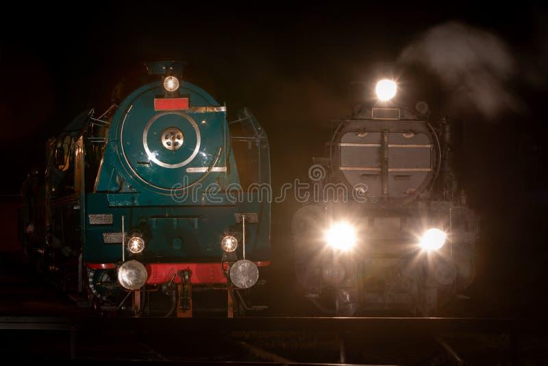 Vooraanzicht van historische stoomlocomotieven in depot verlicht 's nachts stock foto