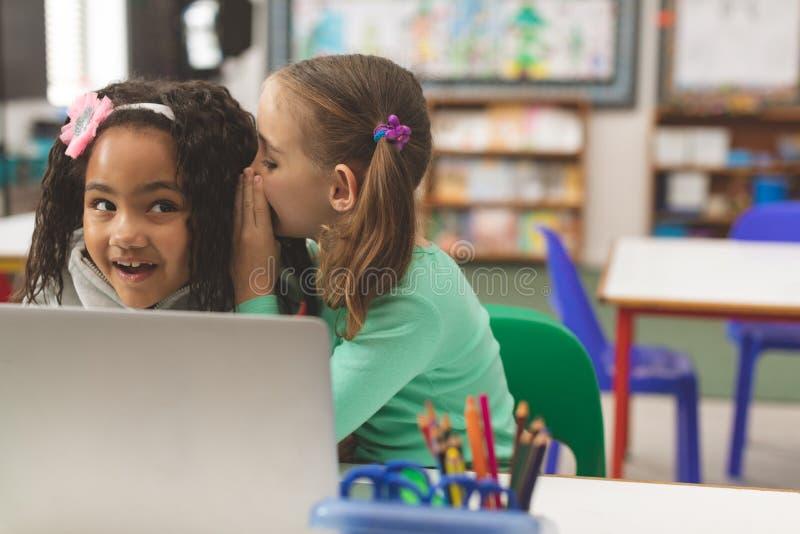Vooraanzicht van Kaukasisch schoolmeisje die een geheim fluisteren in vriendenoor terwijl haar vriend astonis schijnt royalty-vrije stock foto's