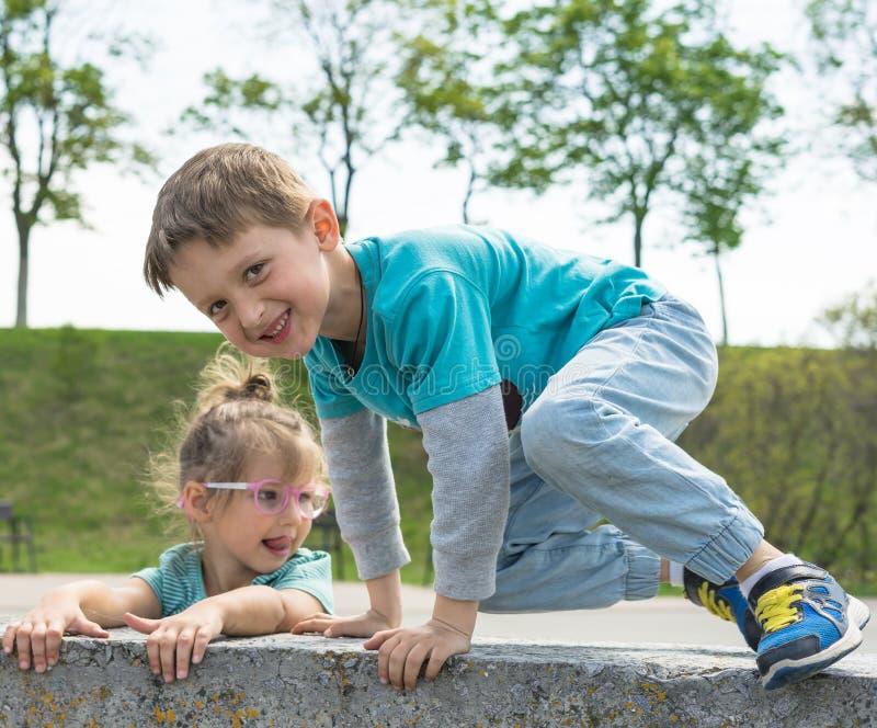 Vooraanzicht van kinderen die tijd in stadspark doorbrengen, jongen en meisjes die aan de steen zitten Gelukkige glimlachende hou royalty-vrije stock foto's