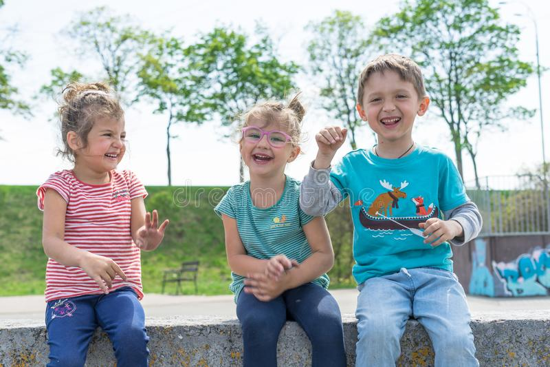 Vooraanzicht van kinderen die tijd in stadspark doorbrengen, jongen en meisjes die aan de steen zitten Gelukkige glimlachende hou stock foto