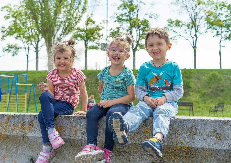 Vooraanzicht van kinderen die tijd in stadspark doorbrengen, jongen en meisjes die aan de steen zitten Gelukkige glimlachende hou stock foto's